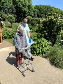 Physio with patient in garden facing camera