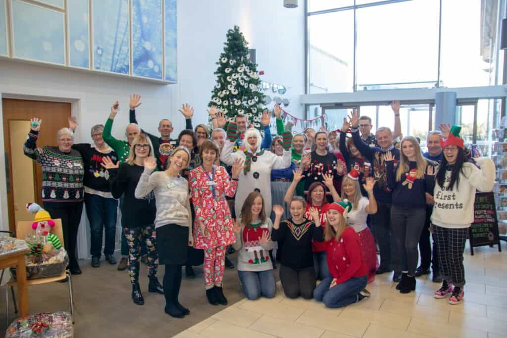 Hopsice staff in Christmas Jumpers around a tree